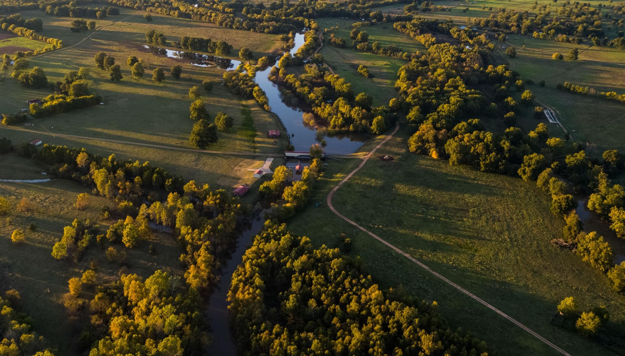 aerial view of creek and grassy fields and trees at tres agues ranch