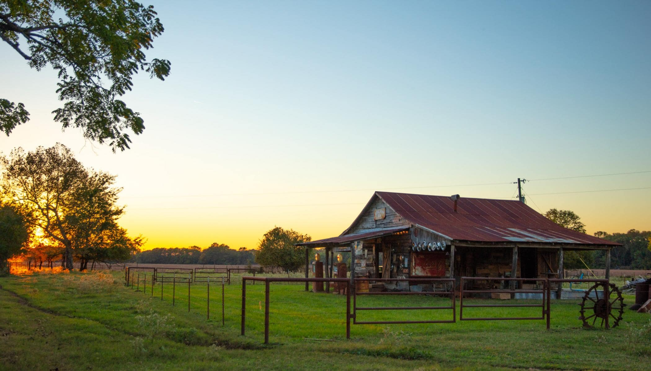 old ranch barn and corral surrounded by trees with colorful sunset behind it