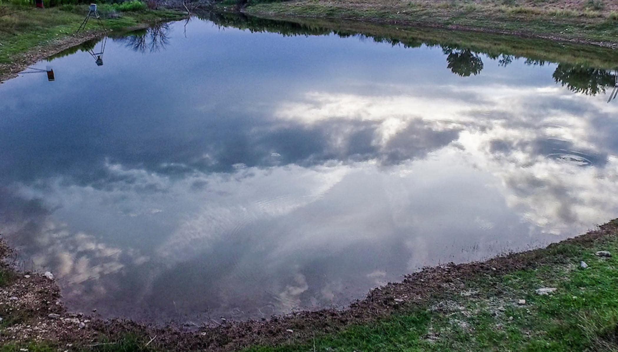 calm pond reflecting clouds and blue sky at saddle ridge ranch