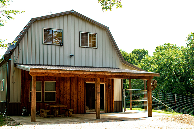 wood and steel barn with covered porch at sugar ridge ranch