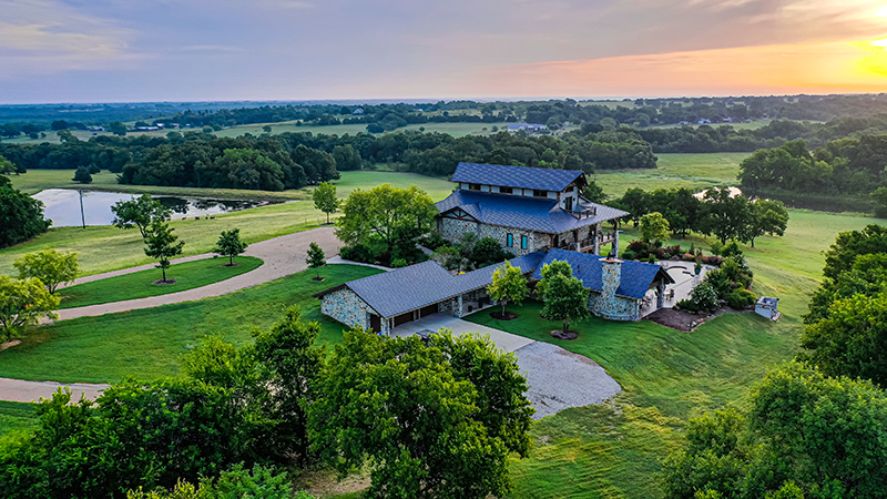 aerial view of main house and lake with colorful sunset at sugar ridge ranch